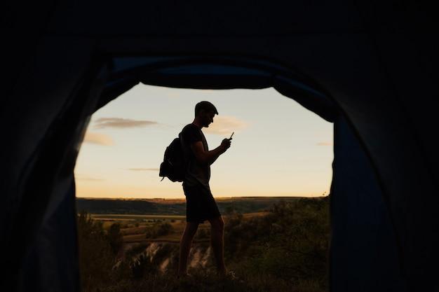 山でキャンプし、テントの近くに立って、テキストメッセージを入力している若い男。