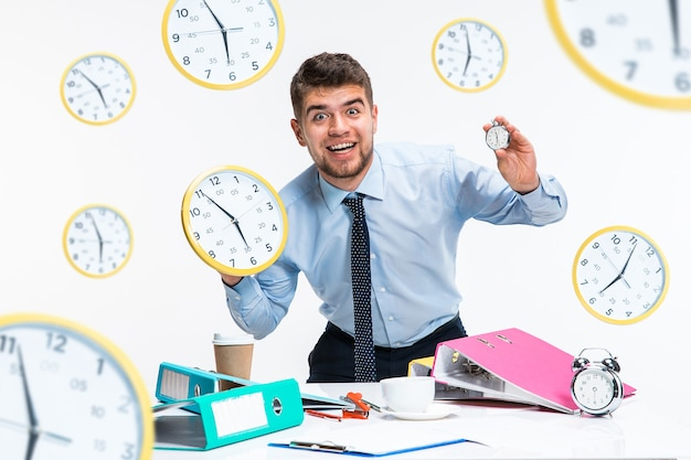 Young man can't wait to go home from the nasty office. holding the clock and waiting five minutes before the end. concept of office worker's troubles, business or problems with mental health.