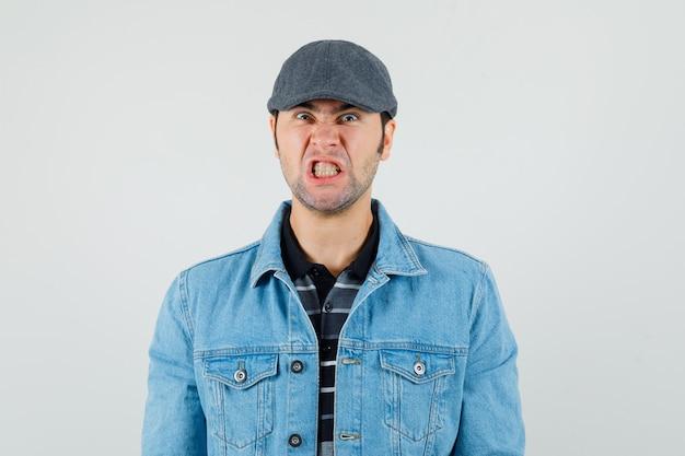Giovane uomo in berretto, t-shirt, giacca stringendo i denti e guardando arrabbiato