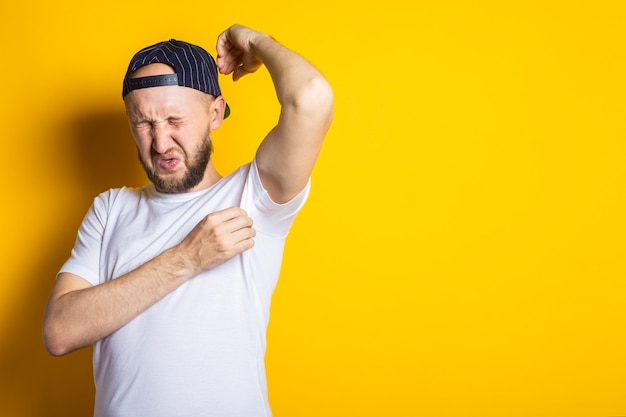 Young man in cap and t-shirt with sweaty and smelly armpits on yellow background.