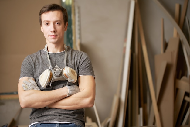 Young man carpenter with arms crossed in workshop