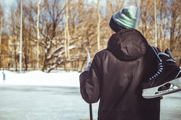 Молодой человек несет на коньках коньки и палку