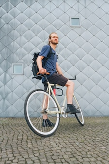 Young man carrying backpack riding bicycle at outdoors
