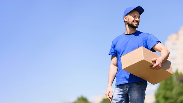Young man carrying delivery parcel