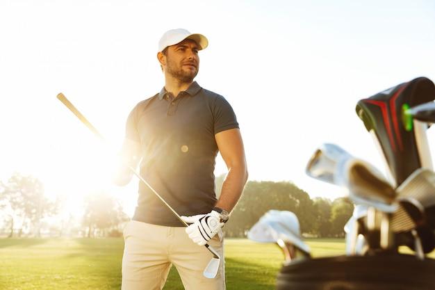 필드에 서있는 동안 골프 클럽을 운반하는 젊은 남자
