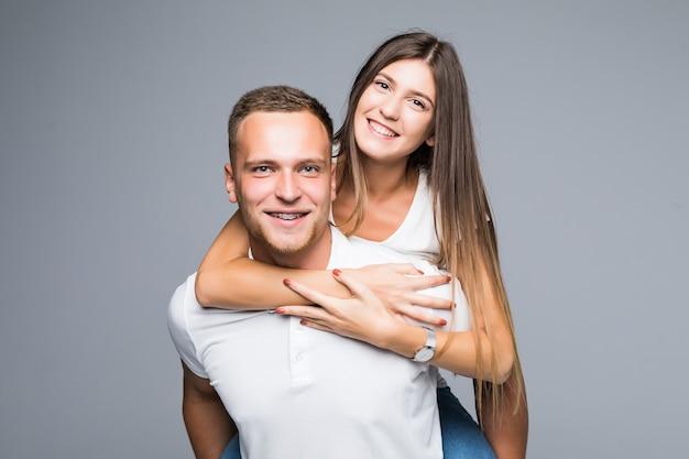 Giovane che porta la sua giovane ragazza sulla schiena in studio