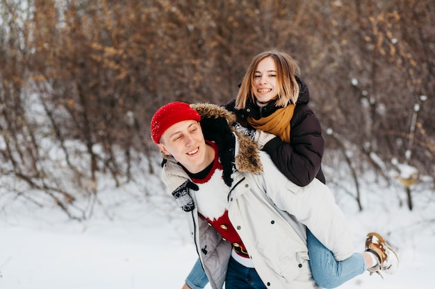 Young man carrying woman on back in winter forest