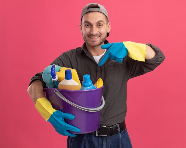 Giovane in abiti casual e berretto in guanti di gomma che tiene secchio con strumenti di pulizia che punta con il dito indice agli strumenti sorridenti felici e positivi in piedi sopra il muro rosa
