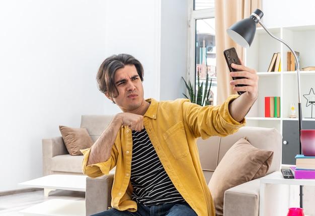 Giovane uomo in abiti casual che fa selfie utilizzando lo smartphone che sembra sicuro seduto sulla sedia in un soggiorno luminoso