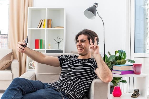 Giovane in abiti casual che fa selfie utilizzando lo smartphone che mostra il segno v felice e allegro seduto sulla sedia in un soggiorno luminoso