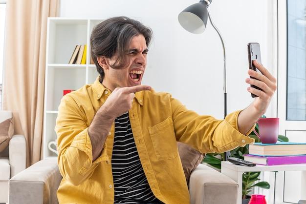 Giovane in abiti casual che fa una videochiamata usando lo smartphone urla arrabbiato e frustrato che si scatena seduto sulla sedia in un soggiorno luminoso