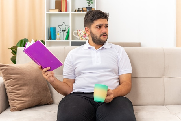Young man in casual clothes holding book and cup looking aside puzzled sitting on a couch in light living room