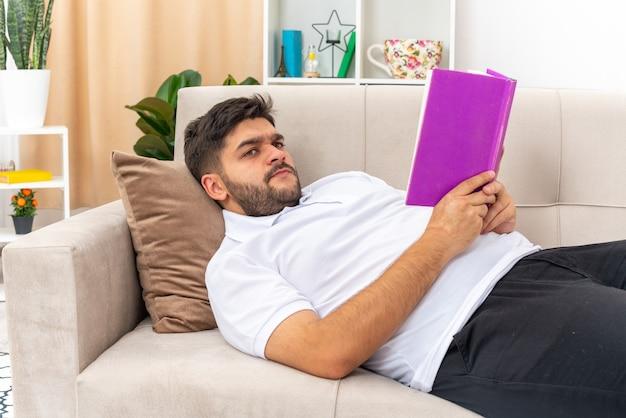 Giovane uomo in abiti casual che tiene in mano un libro che legge con una faccia seria che trascorre il fine settimana a casa sdraiato su un divano in un soggiorno luminoso