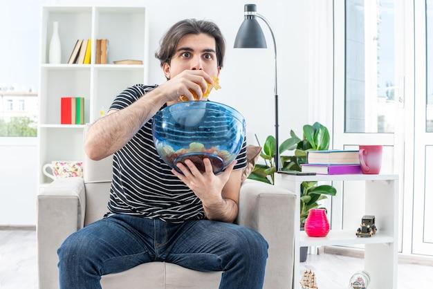Giovane in abiti casual con una ciotola di patatine che mangia guardando stupito e sorpreso seduto sulla sedia in un soggiorno luminoso light
