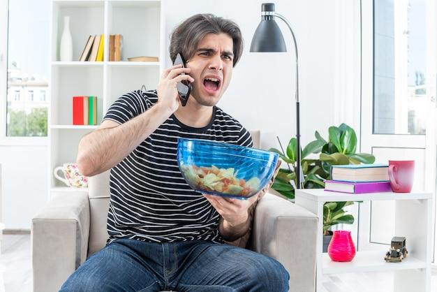Giovane uomo in abiti casual che tiene una ciotola di patatine che grida di essere dispiaciuto mentre parla al telefono cellulare seduto sulla sedia in soggiorno luminoso