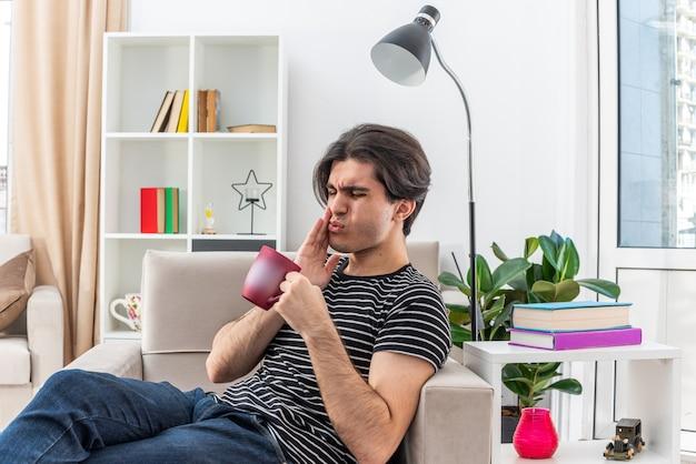 Giovane uomo in abiti casual con in mano una tazza di tè che sembra malato toccando la guancia con mal di denti seduto sulla sedia in un soggiorno luminoso