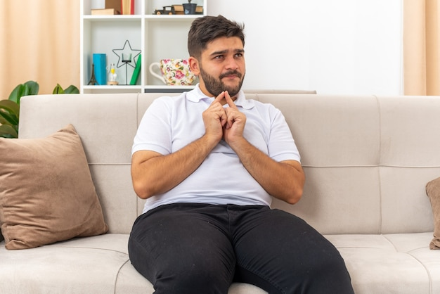 Giovane uomo in abiti casual che si tiene per mano in attesa di una sorpresa seduto su un divano in un soggiorno luminoso