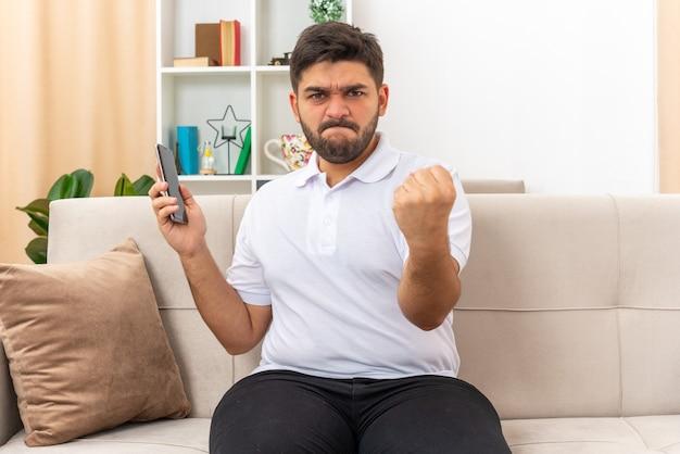 Giovane uomo in abiti casual che tiene il pugno serrato dello smartphone che sembra arrabbiato e frustrato seduto su un divano in un soggiorno luminoso