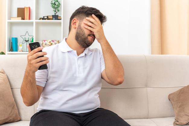 Giovane uomo in abiti casual che tiene in mano uno smartphone che sembra infastidito e stanco che copre il viso con il palmo seduto su un divano in un soggiorno luminoso