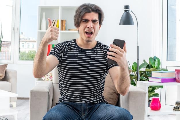 Giovane uomo in abiti casual che tiene in mano uno smartphone che sembra felice ed eccitato che mostra i pollici in su seduto sulla sedia in un soggiorno luminoso