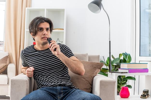 Giovane uomo in abiti casual che tiene il telecomando della tv guardando la tv con un'espressione pensierosa sul viso seduto sulla sedia in un soggiorno luminoso