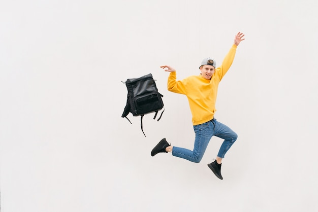 Young man in casual clothes jumps with a backpack