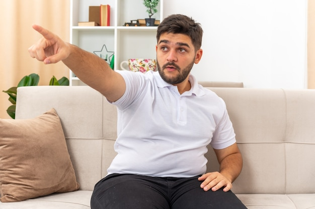 Giovane uomo in abiti casual guardando da parte sorpreso indicando con il dito indice di lato seduto su un divano in soggiorno luminoso
