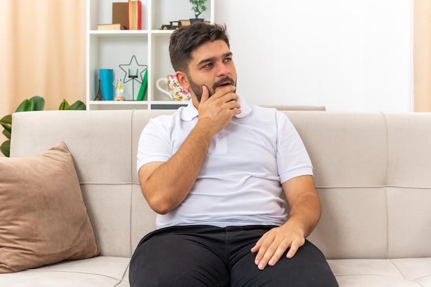 Giovane uomo in abiti casual che osserva da parte con la mano sul mento perplesso seduto su un divano nel soggiorno luminoso