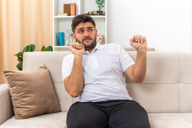 Young man in casual clothes looking aside worried making defense gesture sitting on a couch in light living room