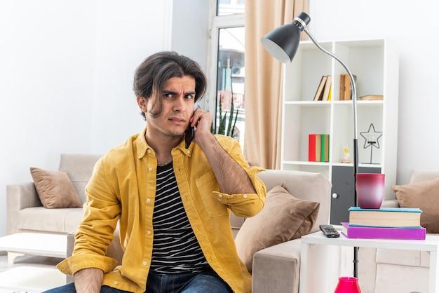 Giovane uomo in abiti casual che sembra confuso mentre parla al telefono cellulare seduto sulla sedia in un soggiorno luminoso
