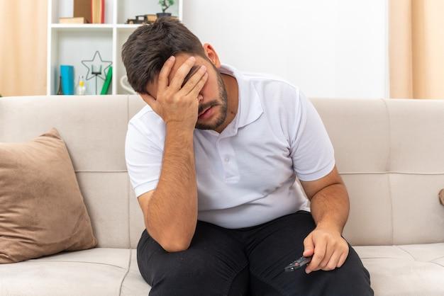 Giovane uomo in abiti casual che sembra depresso coprendosi gli occhi con la mano seduto su un divano in un soggiorno luminoso light