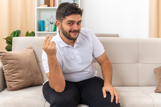 Young man in casual clothes looking making money gesture rubbing fingers smiling slyly sitting on a couch in light living room