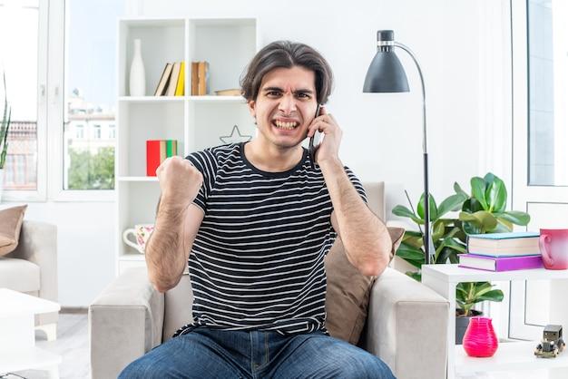 Giovane uomo in abiti casual che guarda con la faccia arrabbiata che mostra il pugno mentre parla al cellulare impazzisce seduto sulla sedia in un soggiorno luminoso