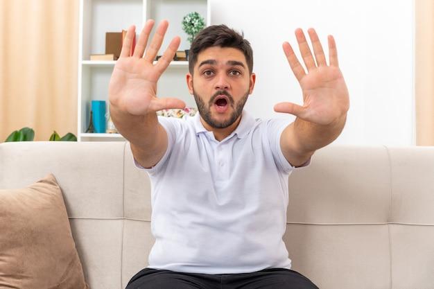 Giovane uomo in abiti casual che sembra preoccupato e spaventato facendo un gesto di arresto con le mani seduto su un divano in un soggiorno luminoso