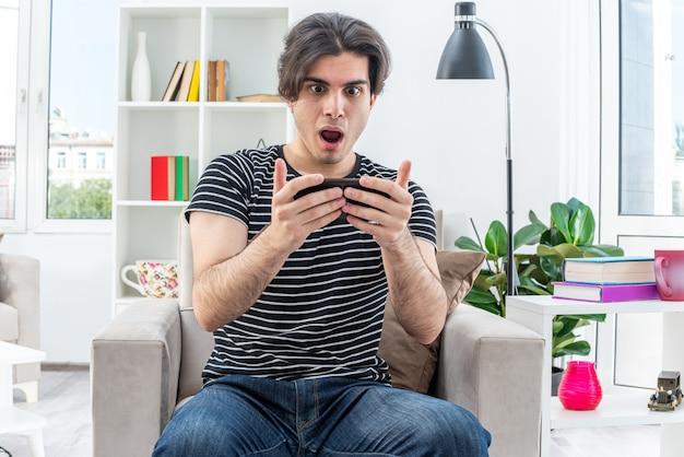 Giovane uomo in abiti casual che gioca usando lo smartphone stupito ed eccitato seduto sulla sedia in un soggiorno luminoso