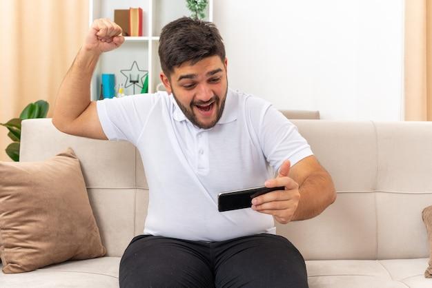 Giovane uomo in abiti casual che gioca usando lo smartphone che stringe il pugno felice ed eccitato seduto su un divano in un soggiorno luminoso
