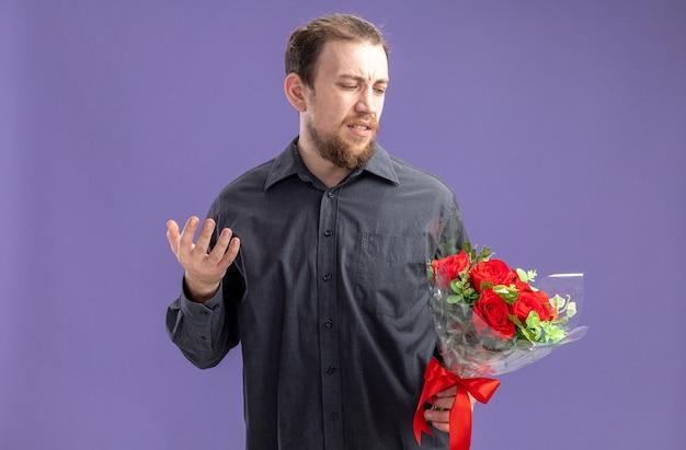 Giovane uomo in abiti casual con bouquet di rose rosse per la sua ragazza guardandolo in piedi confuso su sfondo viola concetto di san valentino