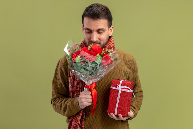 Young man in casual clothes with scarf around neck holding bouquet of red roses and present happy and positivesmiling valentines day concept standing over green background