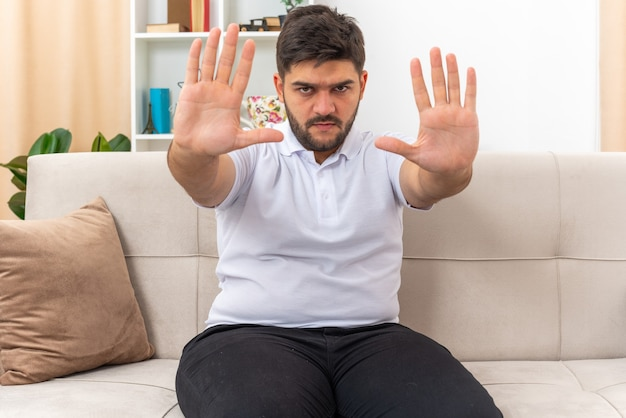 Giovane uomo in abiti casual con una faccia seria che fa un gesto di arresto con le mani seduto su un divano in un soggiorno luminoso