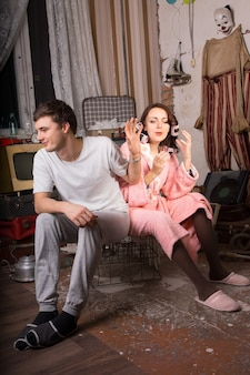 Young man in casual clothing refusing to listen his partner in bath robe while sitting on cage at junk room