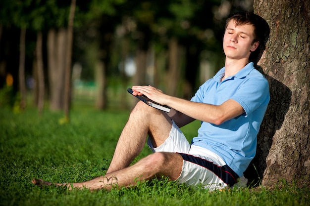 Young man in casual clothing sitting on green grass near tree and reading book in park on summer clear day. inner freedom and happy lifestyle concept
