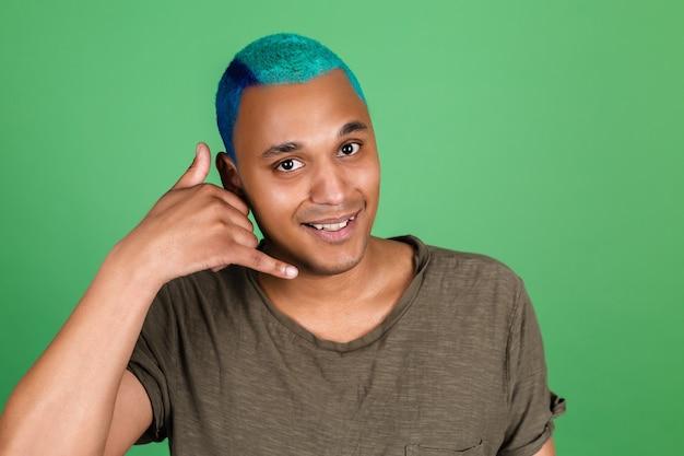 Il giovane in casual sulla parete verde felice con un sorriso fa il gesto del telefono