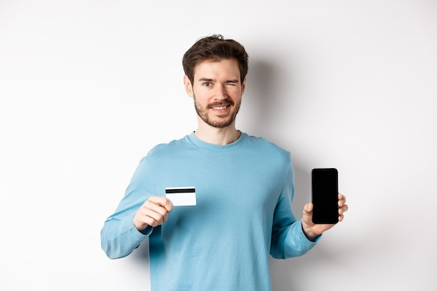 Young man in casual shirt showing empty smartphone screen and plastic credit card, winking and smiling at camera, standing on white background.