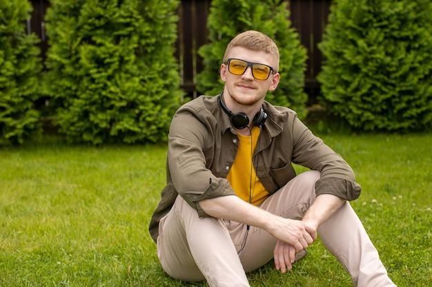黄色い眼鏡をかけてカジュアルな服を着た若い男は、緑の背景で思慮深く見上げる彼の首にヘッドフォンで緑の草の上に座っています。