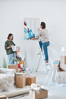 Young man in casualwear standing on stepladder by wall and hanging abstract painting while his wife looking at picture in frame