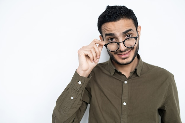 Young man in casualwear taking off his eyeglasses while looking at you in isolation against white space