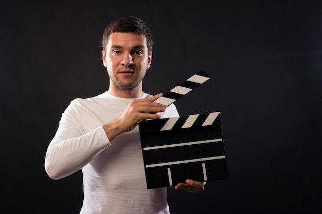 Young man of caucasian appearance is holding a clapperboard.