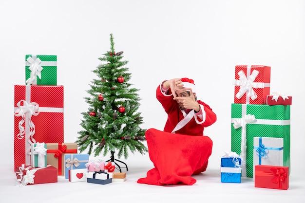 Молодой человек празднует рождество, сидя в земле возле подарков и украшенной рождественской елки