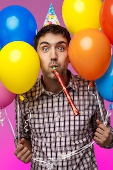若い男が誕生日を祝って、紫色の壁にカラフルな風船を保持しています。