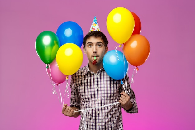 Young man celebrating birthday, holding colorful baloons over purple wall.